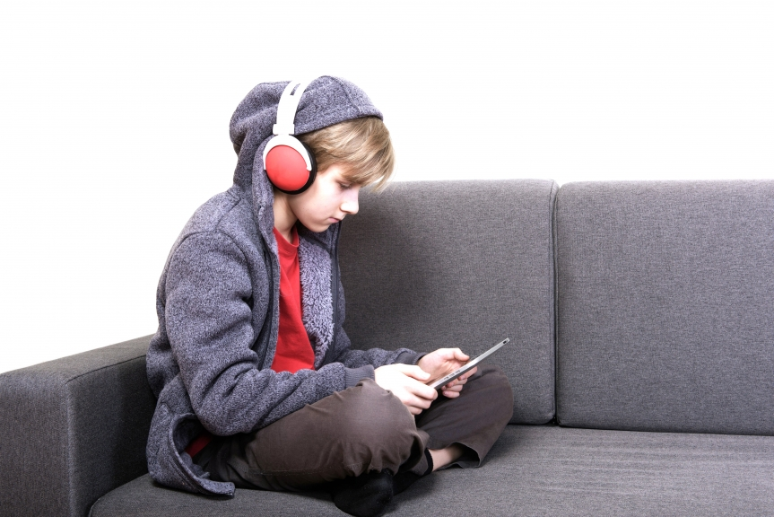 boy with a digital tablet sitting on the couch