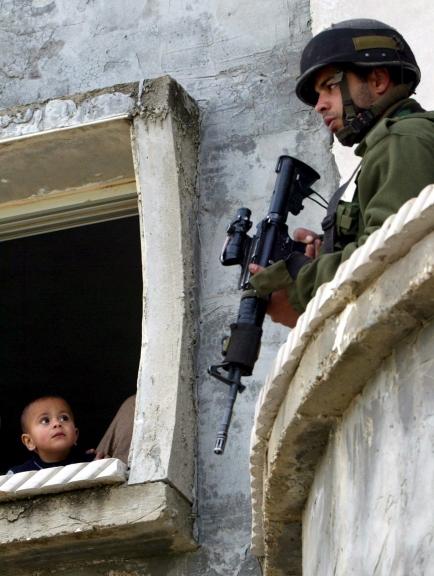 NAB04a NAPLUSA (CISJORDANIA) 20/03/06 : Un ni?o palestinos mira a un soldado israel? apostado en su casa durante una operaci?n militar en el pueblo de Beta junto a la ciudad cisjordana de Naplusa, hoy lunes 20 de marzo. Soldados israel?es registraron el pueblo a primera hora de hoy buscando militantes. EFE/Alaa Badarneh