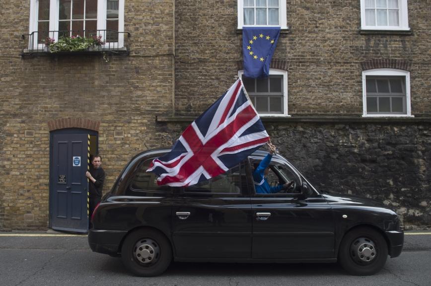 REINO UNIDO UE:HM046 LONDRES (REINO UNIDO) 24/06/2016.- Un taxista londinense ondea una bandera británica mientras circula por una calle donde una bandera europea ondea en una ventana en Londres (Reino Unido) hoy, 24 de junio de 2016. El Reino Unido votó a favor de abandonar la Unión Europea (UE) tras conseguir el 52% del respaldo ciudadano frente al 48% que apoyó la permanencia, en el referéndum celebrado este jueves sobre su relación con el bloque comunitario. EFE/Hannah Mckay