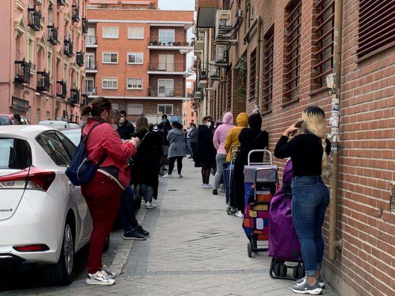 GRAF9028. MADRID, 21/05/2020.- Vista de la fila de clientes que aguardan su turno para entrar al economato de Cáritas en el distrito madrileño de Tetuán, donde familias y personas necesitadas pueden comprar alimentos y otros productos de primera necesidad a precio subvencionado. La crisis causada por la pandemia ha golpeado duro a las comunidades de latinoamericanos en España, con frecuencia en el nivel más frágil de la escala social, y ahora muchos de ellos se ven abocados a la pobreza y a la ayuda para sobrevivir. A menudo atrapados en empleos temporales o informales, los latinos se han visto afectados de forma desmedida por el huracán que se ha llevado por delante, hasta ahora, casi 950.000 empleos. EFE/Rafael Cañas